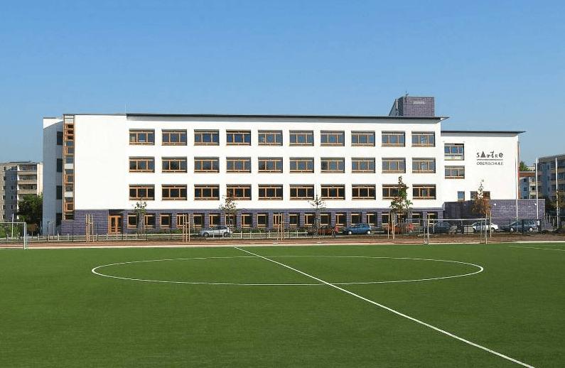 Schulgebäude mit grünem Sportplatz im Vordergrund